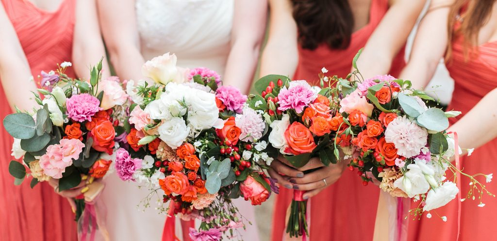 Bridesmaids and bride holds bouquets of flowers in hand.