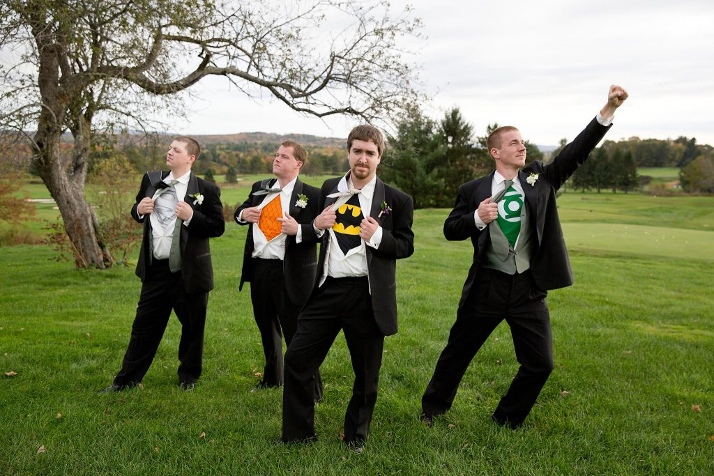 photo of four extremely handsome men (groom and three groomsmen) showing off their super hero teeshirts under their tuxes