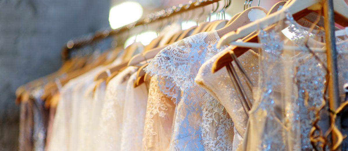 A few beautiful wedding dresses on a hanger.