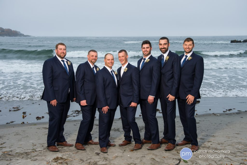 photo of groom and groomsmen in front of crashing waves