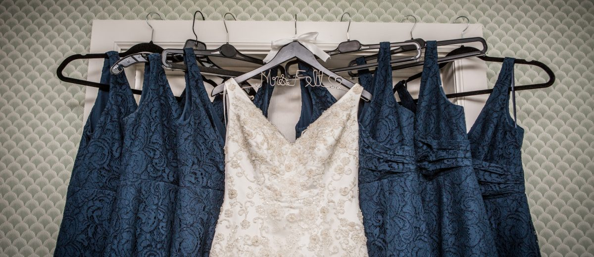 group of blue female dresses with ivory dress in front