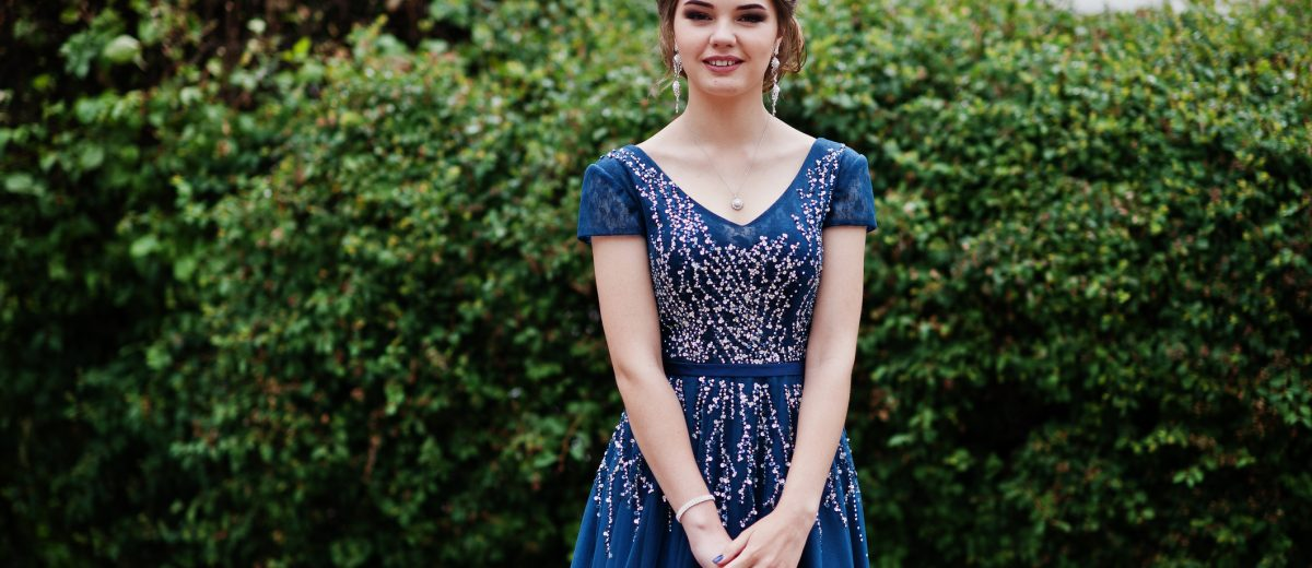 Portrait of a beautiful girl in elegant gown posing outdoors